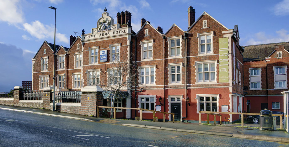 Image depicting the Crewe Arms Hotel building exterior, including carved crest of arms at the top of the building, original redbrick features and windowsills, @1650 branding advertisement, bright sunny day and blue skies