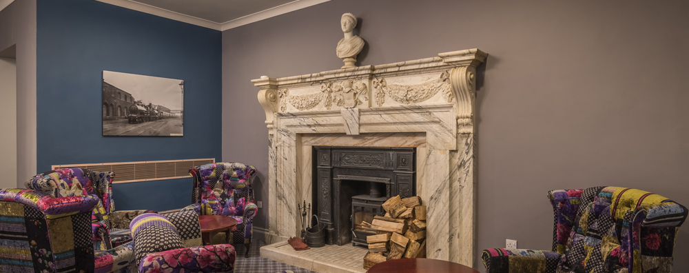 Lounge area showing grand old marble fireplace, multiple arm chairs, a pile of chopped wood next to the wood burning stove, resting atop the fireplace is a renaissance style bust