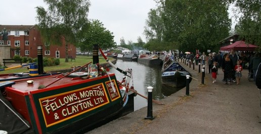 "Etruria Canal Festival showing families walking by the canal. A canal boat is moored to the left of the image which reads ""Fellows, Morton & Clayton, LTD."""