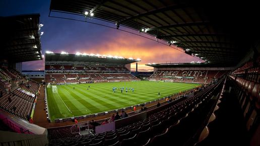 Britannia Stadium, home of Stoke FC. Practice game happening in the evening at dusk, the sky is purple, orange and blue in colours. The angle of the photo is taken from a corner seat, with a slight fish-angle lens, on the pitch the team are huddled in a circle.