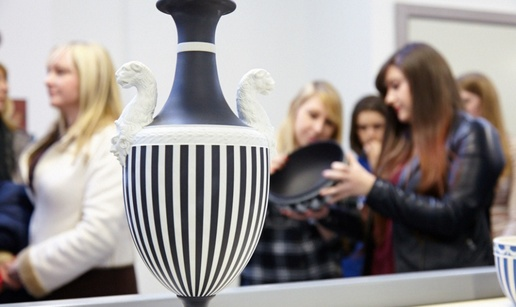 Wedgewood Visitor Centre museum shot, in the foreground a monochromatic-striped vase in the shape of an old greek wine jar is depicted with detailed handles carved in the shape of animals. In the background tour guides and visitors are inspecting another pottery piece.