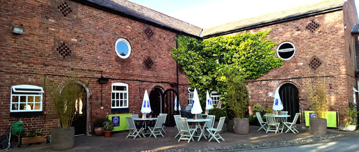 Oldhall Country Club & Spa courtyard showing outdoor seating area for drinks and food. The old redbrick building features many period features including circular windows and ivy crawling up the building in contrast with the redbrick.