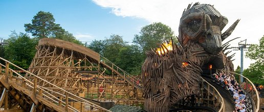"Showing off the ""Wickerman"" ride at Alton Towers Theme Park. Out of a faux-wooden rams head a cart full of visitors hurtles down at breakneck speed in a swerving loop. Next to the ramshead flames spurt out"