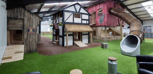 Interior shot of the Play Barn at Amerton Farms. The play area shown shows miniature houses, a grain store silo with a slide. The ground is astroturfed to look like genuine grass.
