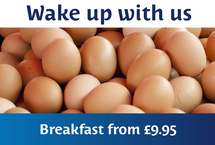 "Fresh chicken eggs ready to be prepared and eaten enclosed by copy that says ""Wake up with us Breakfast from £9.95"""