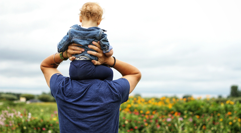 A Father with his child on his shoulders while looking out over a field of flowers
