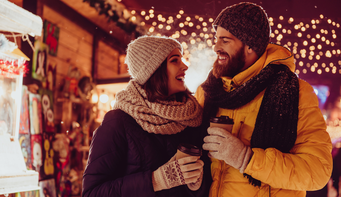 A couple at a Christmas Market. Wearing warm winter clothes and holding takeaway warm drink cups. Fairly lights are in the trees behind them. To the left of the image is a Christmas Market.