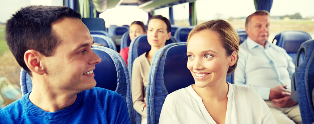 A coach group featuring a couple smiling at each other while riding a coach.