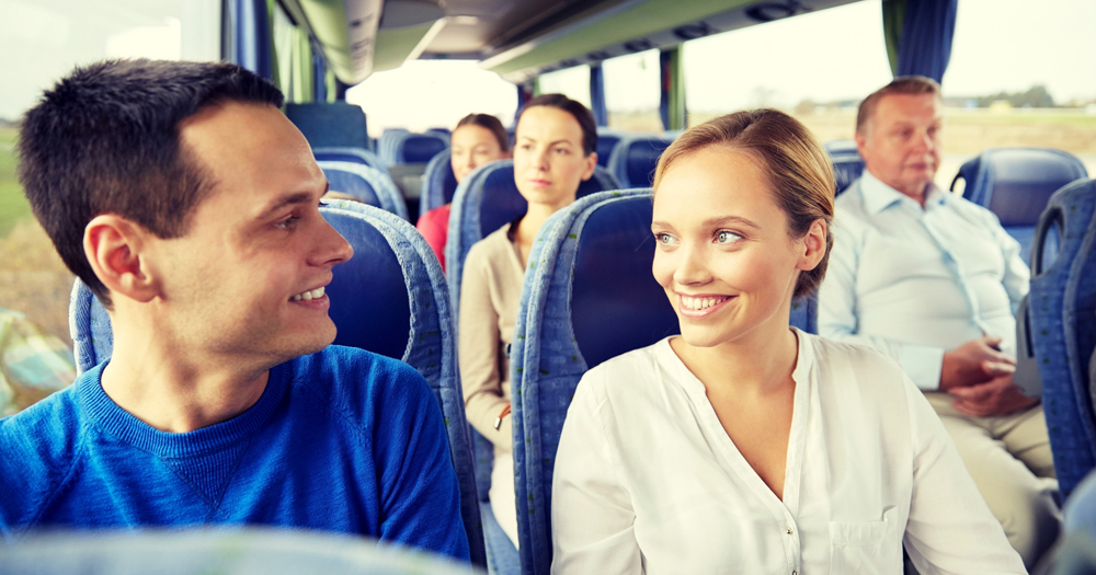 Coach group showing a smiling couple looking into each others eyes while seated in a coach.